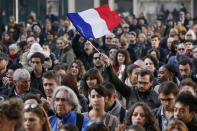A man waves a French flag as several hundred people gather to observe a minute of silence in Lyon, France, November 16, 2015, to pay tribute to the victims of the series of deadly attacks in Paris on Friday. REUTERS/Robert Pratta