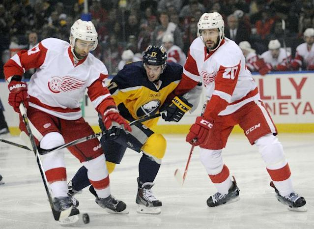 Detroit Red Wings defenseman Kyle Quincy (27) battles for the puck with Buffalo Sabres center Torrey Mitchell (17) as Red Wings left winger Drew Miller (20) defends during the first period of an NHL hockey game in Buffalo, N.Y., Tuesday, April 8, 2014. (AP Photo/Gary Wiepert)