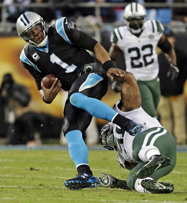 Carolina Panthers' Cam Newton (1) is tackled by New York Jets' Sheldon Richardson during the first half of an NFL football game in Charlotte, N.C., Sunday, Dec. 15, 2013. (AP Photo/Bob Leverone)