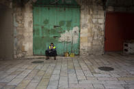 A municipal worker uses his mobile phone in the Old City of Jerusalem, Monday, Dec. 28, 2020 during a third lockdown to curb the spread of the coronavirus. In the early days of the pandemic, a panicked Israel began using a mass surveillance tool on its own people, tracking civilians' mobile phones to halt the spread of the coronavirus. But months later, the tool's effectiveness is being called into question and critics say its use has come at an immeasurable cost to the country's democratic principles. (AP Photo/Maya Alleruzzo)