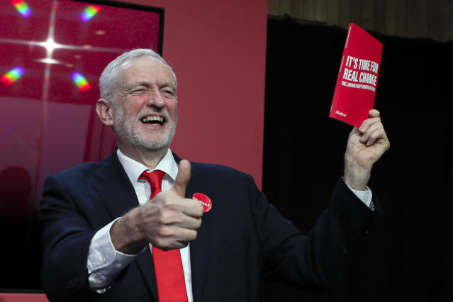 Jeremy Corbyn holding a copy of the manifesto on stage at the launch of Labour's General Election manifesto, 2019. (AP Photo/Kirsty Wigglesworth)