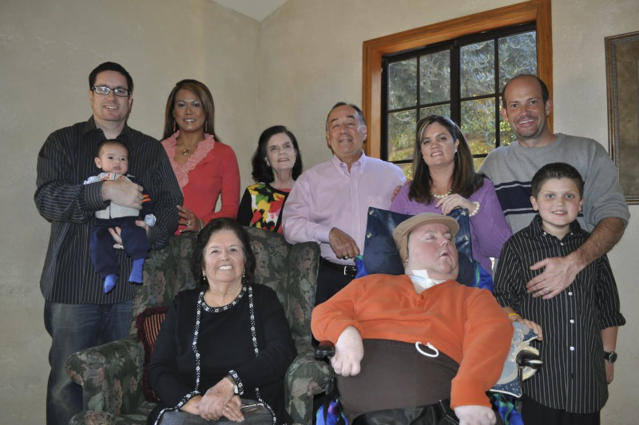 This Nov. 25, 2010 photo provided by Paul Cortez shows Mikey Cortez, front row, center, and his family members on Thanksgiving Day. As his 7-year-old son Mikey lay in a hospital bed on life support, the victim of a drunk driver who had smashed into the car he was riding in, Paul Cortez took the boy's hand and made a solemn promise to God: If his son survived, no matter in what condition, he and his family would always be there for him. Although he would never emerge from the persistent vegetative state his father had found him in that night, Mikey's family was not only there for him but also gave him a full life. A life, as it turned out, not all that different from anybody else's, with cross-country family vacations and visits to Disneyland. (AP Photo/Courtesy Cortez Family)