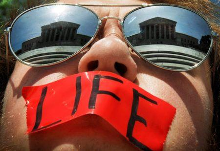 File photo of anti-abortion activist wearing mirrored sunglasses and a piece of tape over his mouth in front of the Supreme Court building in Washington