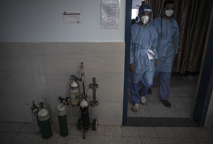 Palestinian doctors wearing protective medical gear walk out of the intensive care unit of the Gaza European Hospital, in the Gaza Strip, Thursday, May 6, 2021. (AP Photo/Khalil Hamra)