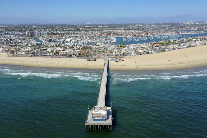 NEWPORT BEACH, CA -- MONDAY, MAY 4, 2020: An aerial view of the Newport Beach pier, where a few surfers and beach-goers enjoy a nice day at the beach despite Gov. Gavin Newsom's hard closure, which is still in place in Newport Beach, CA, on May 4, 2020. (Allen J. Schaben / Los Angeles Times)