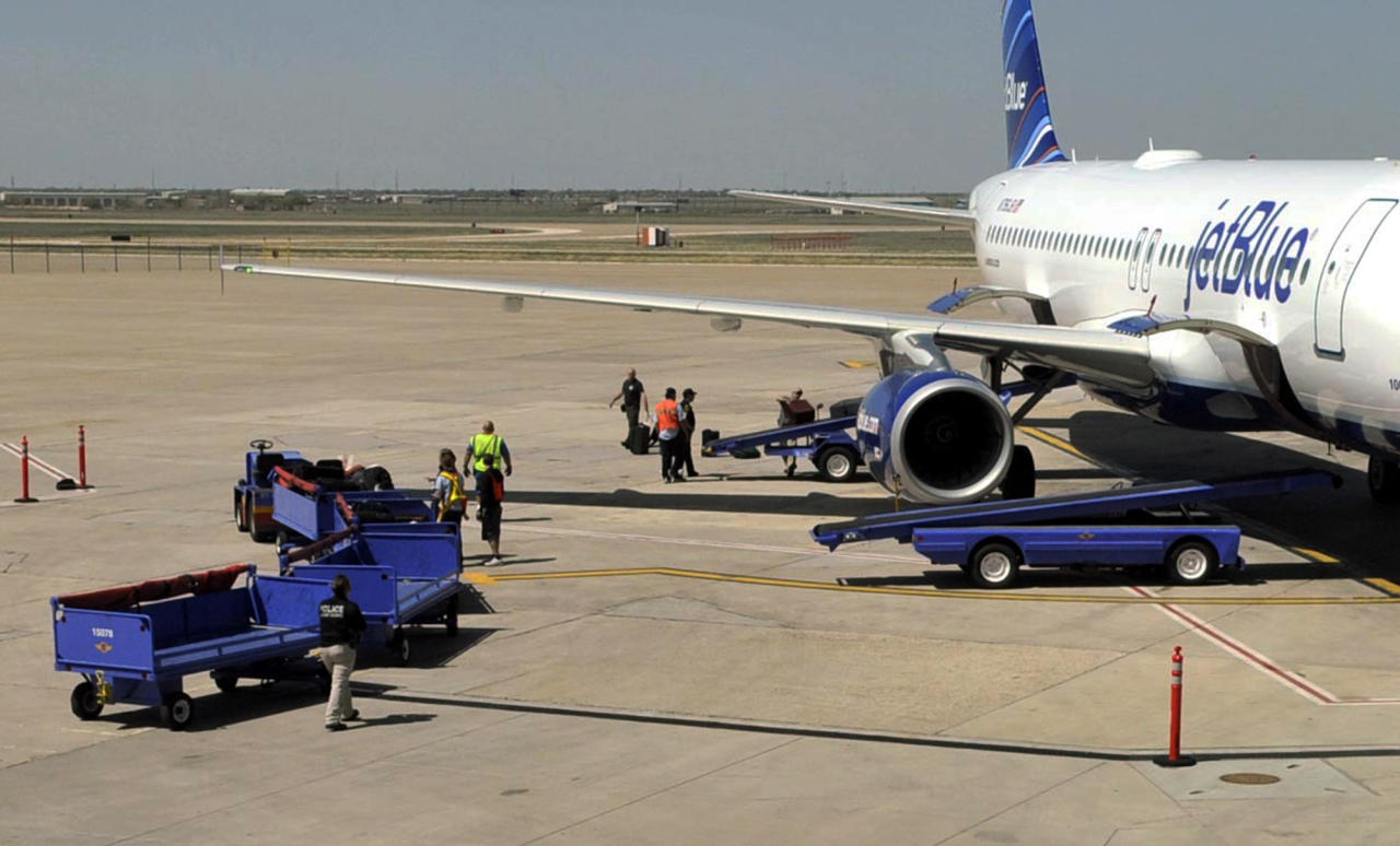 Officials remove baggage from JetBlue flight 191 and begin searching for explosives at Amarillo Rick Husband International Airport in Amarillo, Texas, Tuesday, March 27, 2012 after an unruly pilot caused the flight to make an emergency landing. A JetBlue flight bound for Las Vegas landed unexpectedly in Texas on Tuesday after the captain was taken ill, the airline said. A passenger said a man she and other passengers believed was the captain began yelling about a bomb and had to be restrained. (AP Photo/The Amarillo Globe News, Michael Schumacher)