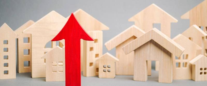 Red arrow up and miniature wooden houses. The concept of rising property prices.