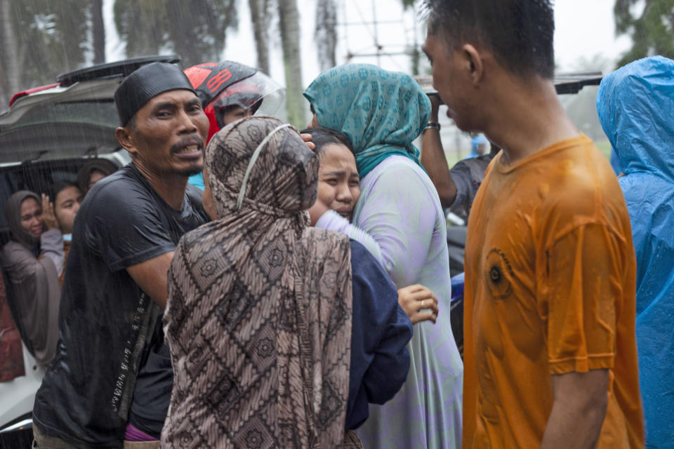 People react at an area affected by an earthquake in Mamuju, West Sulawesi, Indonesia, Friday, Jan. 15, 2021. A strong, shallow earthquake shook Indonesia's Sulawesi island just after midnight Friday, toppling homes and buildings, triggering landslides and killing a number of people. (AP Photo/Yusuf Wahil)