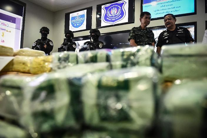 """Thai law enforcers stand behind packages of """"ice"""", or crystal meth, and ketamine during a press conference in May (AFP Photo/Lillian SUWANRUMPHA)"""