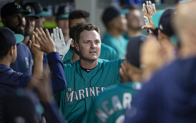 Seattle Mariners' Jay Bruce celebrates in the dugout after hitting a solo home run off Los Angeles Angels starting pitcher Tyler Skaggs during the seventh inning of a baseball game Friday, May 31, 2019, in Seattle. (AP Photo/Stephen Brashear)