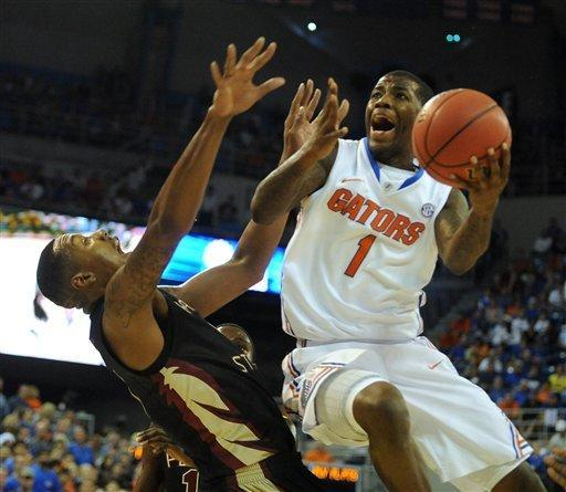 Florida's Kenny Boynton, right, goes over Florida State's Xavier Gibson while trying for two points during the first half of an NCAA college basketball game in Gainesville, Fla., Thursday, Dec. 22, 2011. (AP Photo/ Phil Sandlin)
