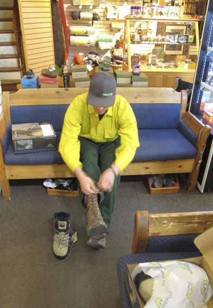 Bradley Boden, a firefighter from Burley, Idaho, tries on new boots at The Elephant Perch, a sports store in Sun Valley, Idaho, on Thursday, Aug. 22, 2013. The store was selling rugged new boots at cost to firefighters like Boden who had spent the last week fighting the massive Beaver Creek Fire that's burned nearby since Aug. 7. (AP Photo/John Miller)