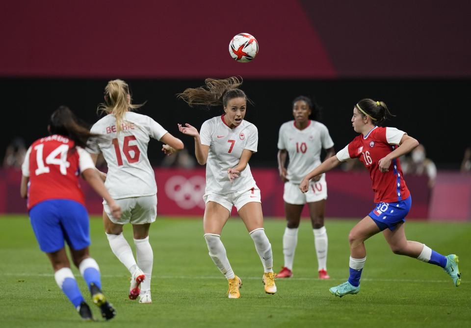 Canada's Julia Grosso, center, heads the ball during a women's soccer match against Chile at the 2020 Summer Olympics, Saturday, July 24, 2021, in Sapporo, Japan. (AP Photo/Silvia Izquierdo)