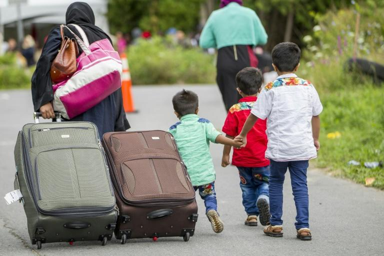 Tens of thousands of asylum seekers, similar to these pictured in August 2017, have entered Canada through unofficial border crossings such as the area on the border between New York and Quebec (AFP Photo/Geoff Robins)
