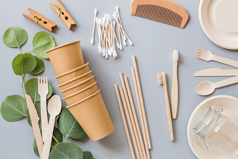 eco natural paper coffee cups, straws, toothbrushes, plates, comb, clothespins flat lay on gray background. sustainable lifestyle concept. zero waste, plastic free items. stop plastic pollution. Top view, overhead, mock up, template