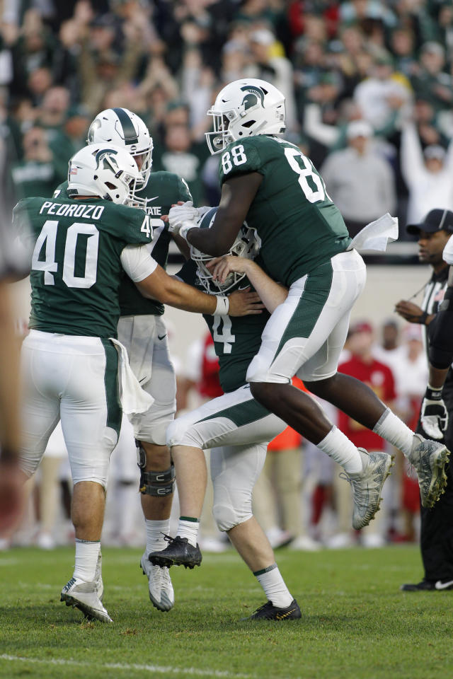 Michigan State's Jude Pedrozo (40), Trenton Gillison (88) and Tyler Hunt, rear, congratulate kicker Matt Coghlin (4) after his tie-breaking 21-yard field goal against Indiana with 5 seconds remaining during the fourth quarter of an NCAA college football game, Saturday, Sept. 28, 2019, in East Lansing, Mich. (AP Photo/Al Goldis)