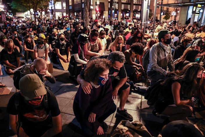 """People take a knee on the 16th Street Mall as they protest the grand jury decision in the Breonna Taylor case on September 23, 2020 in Denver. <p class=""""copyright"""">Michael Ciaglo/Getty Images</p>"""