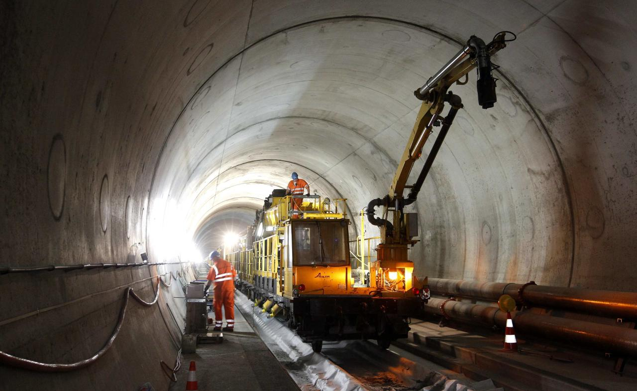 A worker stands on the special train 'Helvetia' in the NEAT Gotthard Base tunnel near Erstfeld May 7, 2012. The train, which is 481 metres (1578 ft) long and weighs 787 tons, is constructed to produce concrete for the installation of the railway tracks in the tunnel. Crossing the Alps, the world's longest train tunnel should become operational at the end of 2016. The project consists of two parallel single track tunnels, each of a length of 57 km (35 miles ) REUTERS/Arnd Wiegmann   (SWITZERLAND - Tags: BUSINESS CONSTRUCTION EMPLOYMENT TRAVEL)
