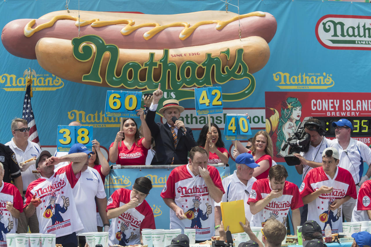 <p>Mater of Ceremony George Shea, top center, announces that reigning champion Joey Chestnut, bottom center, is winning the men's competition of the Nathan's Famous Fourth of July hot dog eating contest in the final seconds of the competition, Wednesday, July 4, 2018, in New York's Coney Island. Defending champion Joey Chestnut broke his own world record by eating 74 hot dogs in 10 minutes. (Photo: Mary Altaffer/AP) </p>