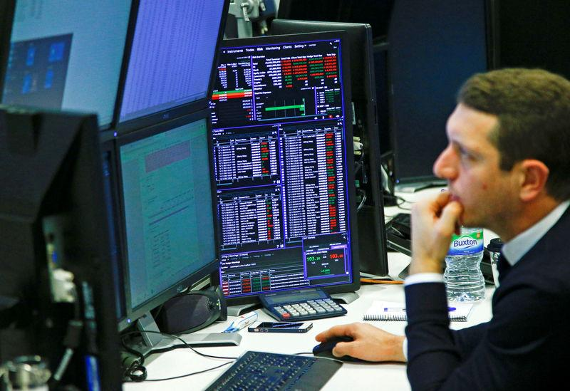 Traders work at their desks whilst screens show market data at CMC Markets in London