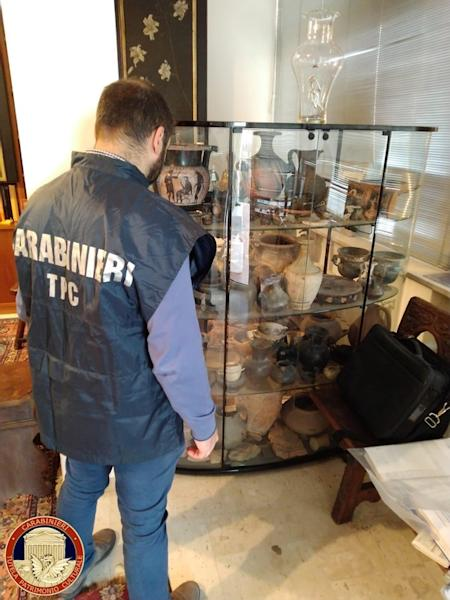 Carabinieri military policeman looks at artefacts in a display case in Cosenza