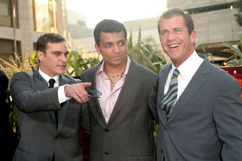 """Actors Joaquin Phoenix and Mel Gibson with director M. Night Shyamalan at the """"Signs"""" World Premiere at Alice Tully Hall  in New York City. July 29, 2002.  Photo: Evan Agostini/ImageDirect"""