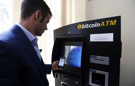 George Rotariu uses the first bitcoin ATM in downtown Bucharest June 27, 2014. REUTERS/Bogdan Cristel