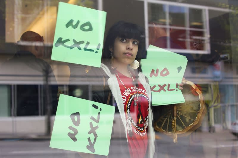 FILE PHOTO: A protester holds signs in opposition to the Keystone XL pipeline as she joins Native American leaders and climate activists demonstrating inside a Chase Bank location in Seattle