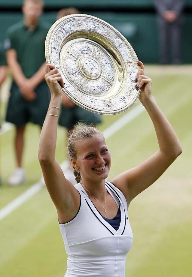 Petra Kvitova of the Czech Republic holds her trophy aloft after defeating Russia's Maria Sharapova in the ladies' singles final at the All England Lawn Tennis Championships at Wimbledon, Saturday, July 2, 2011.(AP Photo/Kirsty Wigglesworth)