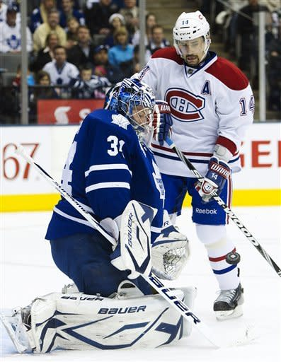 Toronto Maple Leafs goalie James Reimer makes a save as Montreal Canadiens forward Tomas Plekanec, right, looks for the rebound during the second period of an NHL hockey game, Saturday, Feb. 11, 2012, in Toronto. The Canadiens won 5-0. (AP Photo/The Canadian Press, Nathan Denette)