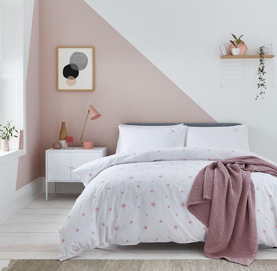 """<p>A lovely girls' bedroom idea is this pink and white colour scheme. The soft pink works in harmony with the crisp white, while the diagonal paint effect creates a feature wall. White furniture and oak shelving completes the look.</p><p>Pictured: Scattered Stars Pink and White Bed Linen in Organic Cotton Percale, <a href=""""https://www.thefinecottoncompany.com/scattered-stars-white-pink-bed-linen-scattered-stars-white-and-pink-organic-cotton-bedding-p1394"""" rel=""""nofollow noopener"""" target=""""_blank"""" data-ylk=""""slk:The Fine Cotton Company"""" class=""""link rapid-noclick-resp"""">The Fine Cotton Company</a></p>"""