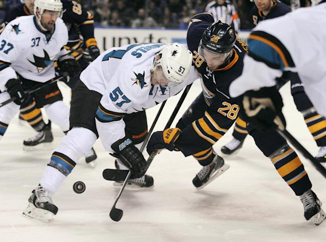 San Jose Sharks center Tommy Wingels (57) wins a face-off against Buffalo Sabres center Zemgus Girgensons (28), of Latvia, during the second period of an NHL hockey game in Buffalo, N.Y., Friday, Feb. 28, 2014. (AP Photo/Gary Wiepert)