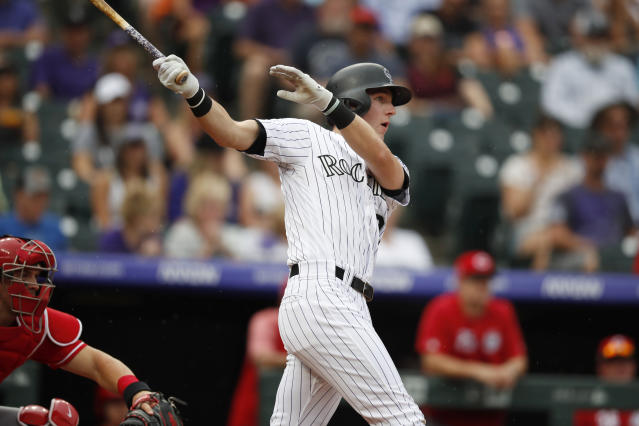 Colorado Rockies' Ryan McMahon follows the flight of his double to drive in two runs off Cincinnati Reds starting pitcher Tyler Mahle in the first inning of a baseball game Sunday, July 14, 2019, in Denver.(AP Photo/David Zalubowski)