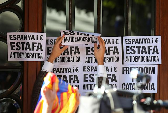 "<p>A crowd of protesters paste posters reading ""Spain and Euro, Anti-democratic Fraud"" to the Catalan region's economy ministry building after junior economy minister Josep Maria Jove was arrested by Spanish police during a raid on several government offices, in Barcelona, Spain, Sept. 20, 2017. (Photo: Albert Gea/Reuters) </p>"
