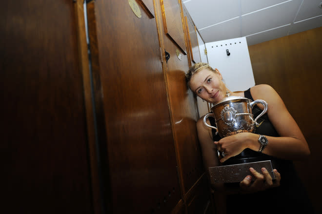 Russia's Maria Sharapova poses with her trophy in the clockrooms after winning against Italy's Sara Errani the Women's Singles final tennis match of the French Open tennis tournament at the Roland Garros stadium, on June 9, 2012 in Paris.   AFP PHOTO / POOL SINDY THOMASSINDY THOMAS/AFP/GettyImages