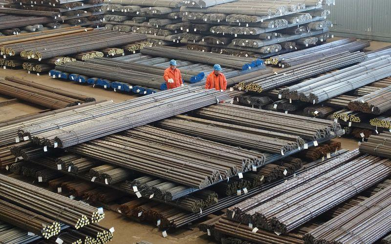 Workers check steel products at a factory in Dalian