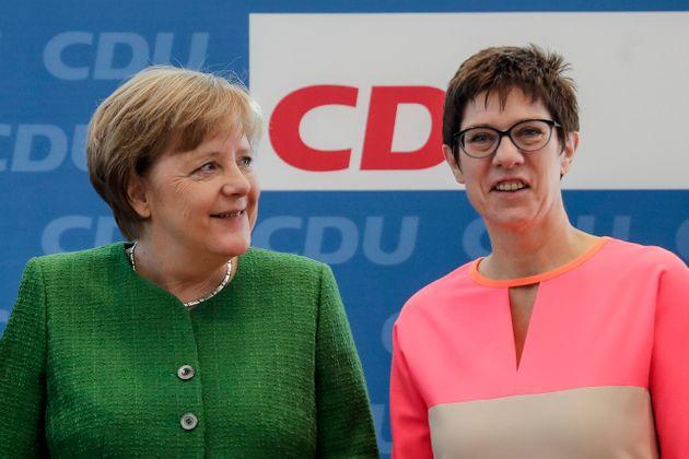 FILE - In this Monday, Feb. 19, 2018 file photo German Chancellor Angela Merkel, left, and the governor of German Saarland state and designated Christian Democratic Union party General Secretary, Annegret Kramp-Karrenbauer, right, attend a party leaders' meeting in Berlin, Germany. The CDU's general secretary since February, Kramp-Karrenbauer _ often called 'AKK' _ is a Merkel ally and the closest to her centrist stance. She touts her own lengthy experience in regional government, which saw her become the first woman to become a state's interior minister, or top security official, and serve as governor of western Saarland state. (AP Photo/Markus Schreiber, file)