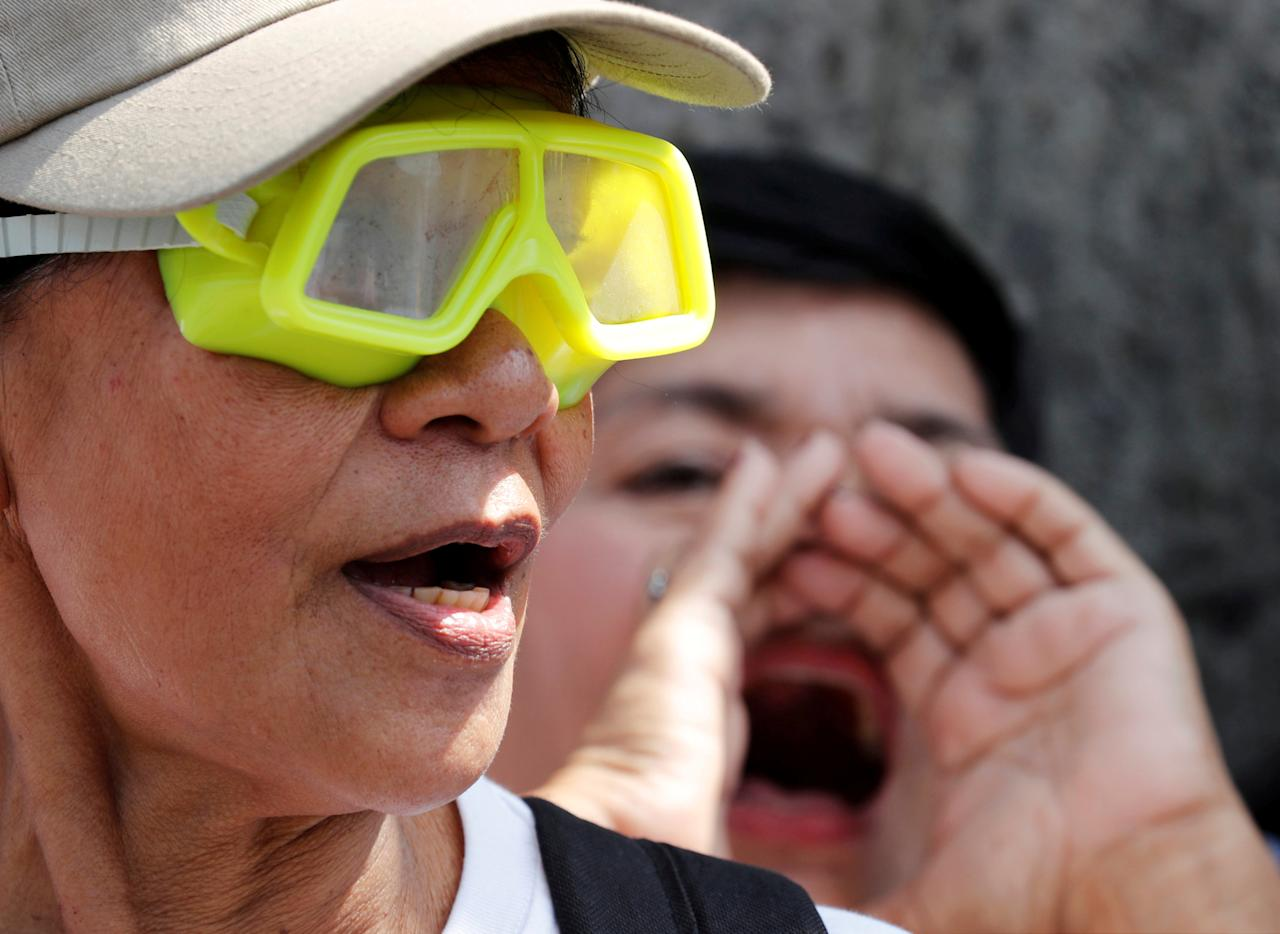 Members of Akbayan Party List activist group wear goggles and chant slogans during a protest about China's naming of undersea features in Benham Rise in the disputed South China Sea, outside the Department of Foreign Affairs in Manila, Philippines February 20, 2018.  REUTERS/Erik De Castro     TPX IMAGES OF THE DAY