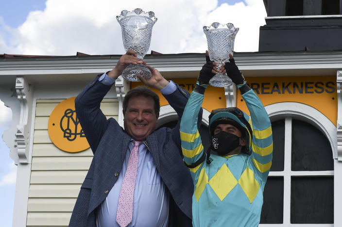 Trainer Michael J. Maker, left, and jockey Joel Rosario hold trophies after Rosario rode Army Wife to win the Black-Eyed Susan Stakes horse race at Pimlico Race Course, Friday, May 14, 2021, in Baltimore. (AP Photo/Will Newton)