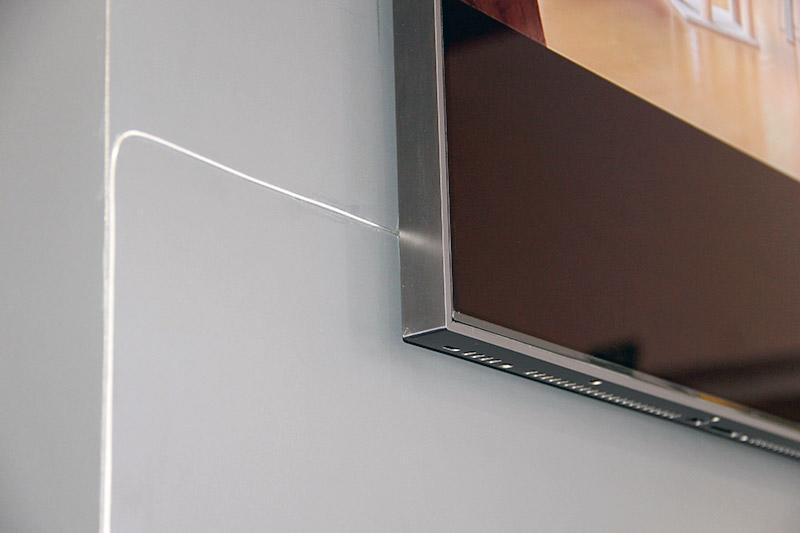 It's so thin that it isn't much of an eyesore if you were to tape it to the wall. The cable is in-wall rated, by the way.