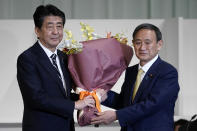 FILE - In this Sept. 14, 2020, file photo, Japan's then Prime Minister Shinzo Abe, left, receives flowers from then Chief Cabinet Secretary Yoshihide Suga after Suga was elected as new head of Japan's ruling party at the Liberal Democratic Party's (LDP) leadership election in Tokyo. Japan's new Prime Minister Suga heads to Vietnam and Indonesia on Sunday, Oct. 18, 2020, on his first overseas foray since taking over from his former boss Abe last month. (AP Photo/Eugene Hoshiko, Pool, File)