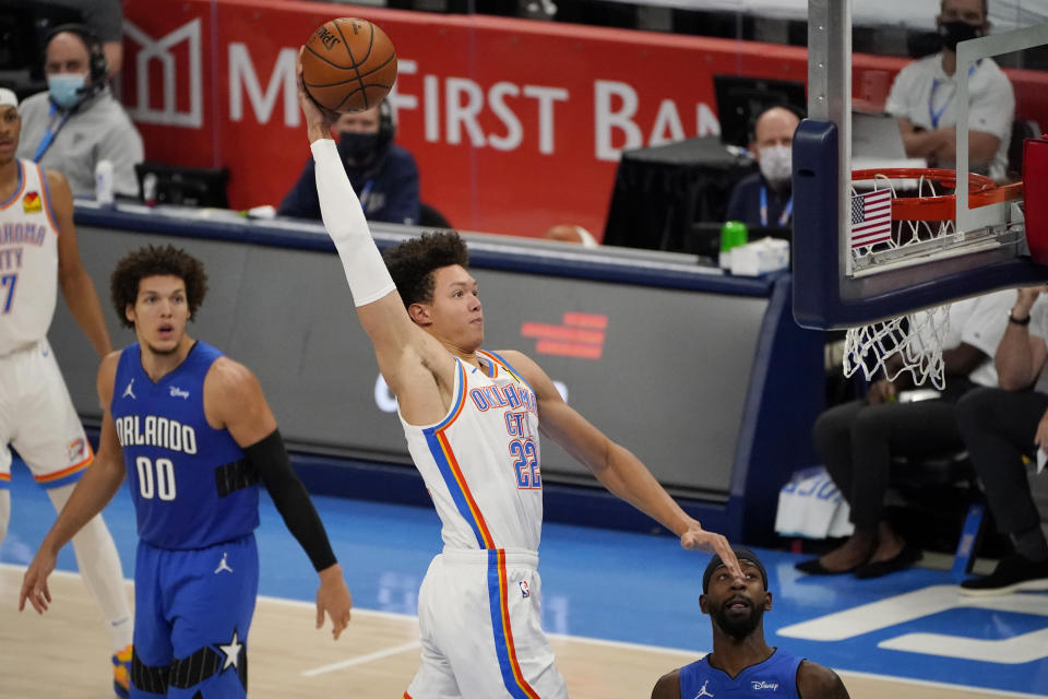 Oklahoma City Thunder forward Isaiah Roby (22) goes up for a dunk between Orlando Magic forward Aaron Gordon (00) and guard Terrence Ross during the second half of an NBA basketball game Tuesday, Dec. 29, 2020, in Oklahoma City. (AP Photo/Sue Ogrocki)