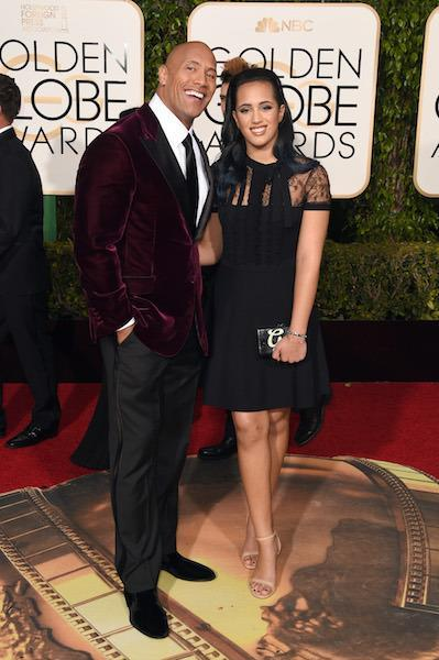 """Dwayne """"The Rock"""" Johnson in a maroon velvet tuxedo jacket with black trousers at the 73rd Golden Globe Awards."""