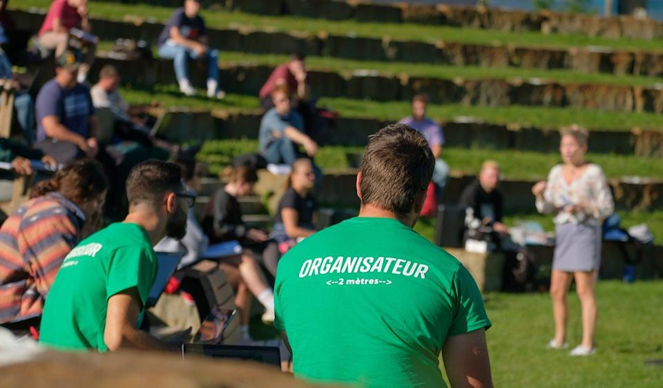 "<span class=""caption"">An orientation week organizer wearing a shirt promoting physical distancing of two metres sits in a new outdoor ampitheatre at Université de Sherbrooke piloted this past fall.</span> <span class=""attribution""><span class=""source"">(Michel Caron/UdeS ) </span></span>"