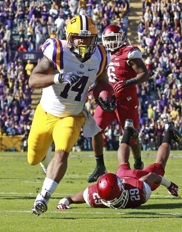 LSU running back Terrence Magee (14) heads for the end zone in front of Arkansas cornerback Jared Collins (29) for a touchdown in the first half of an NCAA college football game in Baton Rouge, La., Friday, Nov. 29, 2013. (AP Photo/Bill Haber)