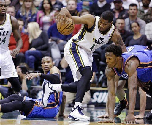 Utah Jazz's Derrick Favors, center, grabs a loose ball as Oklahoma City Thunder's Russell Westbrook, left, and Hasheem Thabeet, right, watch in the first quarter during an NBA basketball game, Tuesday, April 9, 2013, in Salt Lake City. (AP Photo/Rick Bowmer)