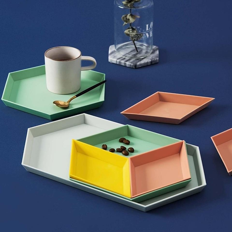 "<h3><a href=""https://amzn.to/2CIwNmW"" rel=""nofollow noopener"" target=""_blank"" data-ylk=""slk:Stackable Geometric Trays"" class=""link rapid-noclick-resp"">Stackable Geometric Trays</a></h3><br>These colorful trays are ready to work some stylish multipurpose as jewelry catchalls, desk organizers, or food servers. <br><br><strong>UNIKON</strong> Stackable Geometric Trays (Set of 4), $, available at <a href=""https://amzn.to/2CIwNmW"" rel=""nofollow noopener"" target=""_blank"" data-ylk=""slk:Amazon"" class=""link rapid-noclick-resp"">Amazon</a>"