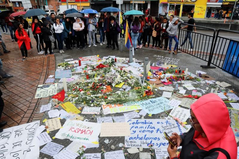 People gather around placards, candles and flowers to honour Dilan Cruz, a teenage demonstrator who died after being injured by a tear gas canister during an initial strike last week, in Bogota