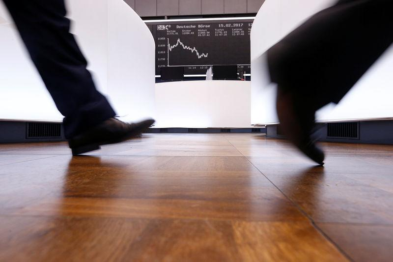 A trader walks past the German DAX Index board on the trading floor at the Frankfurt stock exchange