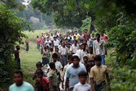 Men walk at a Rohingya village outside Maugndaw in Rakhine state